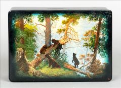 A Russian lacquered papier mache box The hinged rectangular lid decorated with bears in a wood,