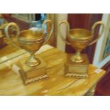 A pair of faux Empire style trophy cups with handles on base  light wooden twin handled faux