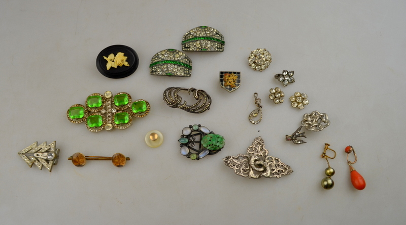 An Arts and Crafts dress clip set with carved green stone plaque,