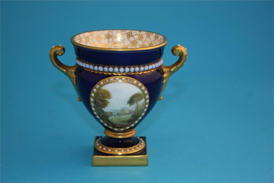 Lot 16 - A small Royal Worcester Campagna shaped vase, the front decorated in enamels with a view of