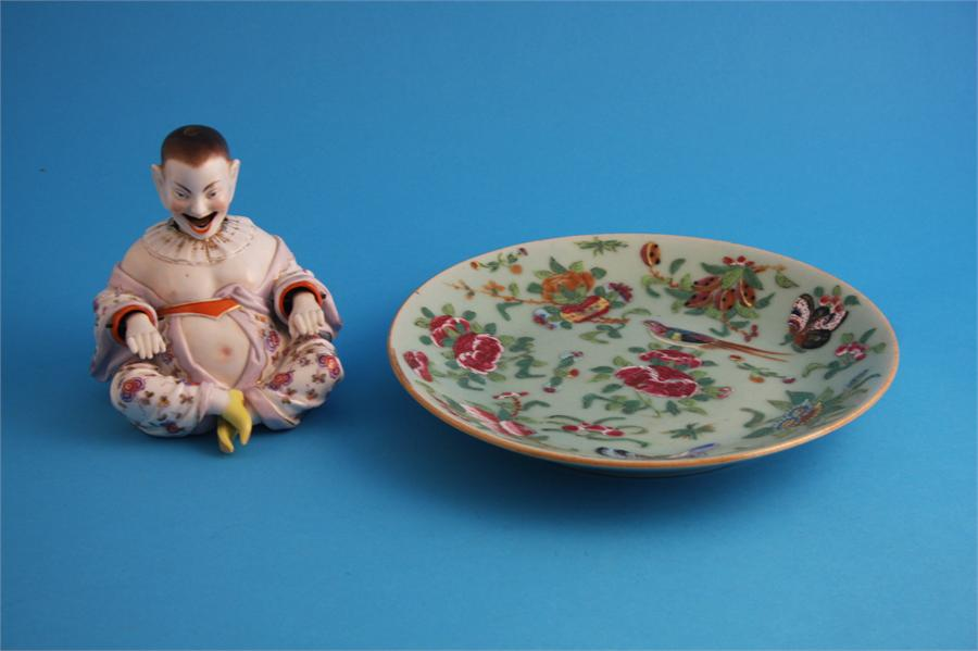 Lot 30 - A Chinese Canton enamel circular plate and a porcelain seated Chinese nodding figure.  25 cm