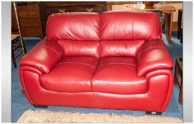 Modern Two Seater Red Leatherette Sofa, 62'' in width, 36'' in depth.