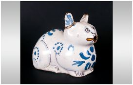 Rare Antique Delftware Cat Of Unusual Reclining Form decorated in blue hues and yellow highlights to