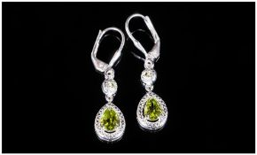 Pair of Peridot Articulated Drop Earrings, pear cut in a millgrain mount, set below a small round