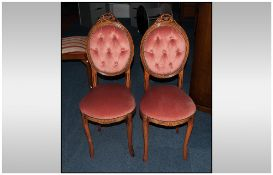 A Pair of French Beech Walnut Stained Music Chairs with a carved medallion button back and pink