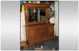An Edwardian Golden Oak Mirrored Back Sideboard with a shaped bevelled mirror.