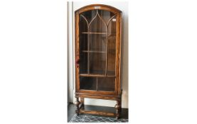 1930's Oak Single Door Display Cabinet With Astral Glazed Door with shaped domed top on turned legs.