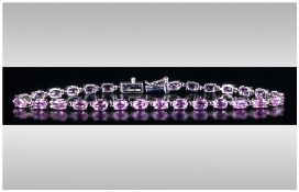 Pink Sapphire Tennis Bracelet, a row of oval cut, rare, pink sapphires, totalling 7cts, set in
