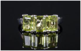 Peridot Trilogy Ring, three octagon cut, bright green peridots, totalling 3cts set in platinum