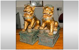 A Pair of Chinese Style Gilded Foo Dogs in the classical style. On a rectangular base.