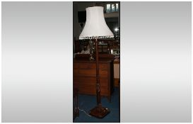 A Carved Stained Beech Art Deco Style Standard Lamp on a square base with carved motifs with tassel