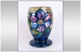 Moorcroft 'Clematis' Pattern Ovoid Vase with spread foot, pale pink and bluish purple flowers on a