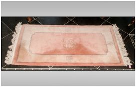 Small Rectangular Wool Rug, predominantly pale pink in colour with beige border. 140x70cm
