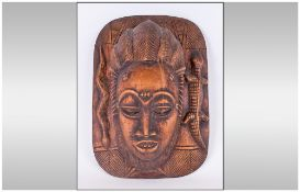 An African Carved Ornate Wall Mask depicting a woman with an elaborate hair style,. With openings to