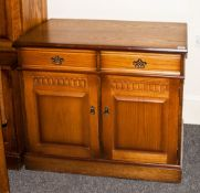 An Oak Two Drawer Cupboard with scratch carving to the dorr and brass drop handles. 40 inches high