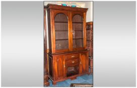 An Edwardian Mahogany Glazed Book Case on Dog Kennel Base. With 2 Shaped Glazed Doors Above, with