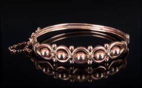 A Victorian 9ct Gold Hinged Bangle with Safety Chain. Marked 9ct. Baubles and Knot Design. 9.8