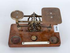 A Set Of Brass Postal Scales by Windle E Blythe. On Oak Base. Weight Missing