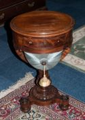 A William IV Mahogany Ladies Round Shaped Sewing Table with sliding basket raised on a turned column
