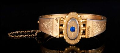 Early Victorian Gilt Metal Hinged Bangle with sapphire set centre & chased decoration to shoulders