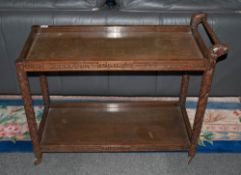 A Far Eastern Teak Carved Tea Trolley with dragon leg supports with carved floral borders & legs.