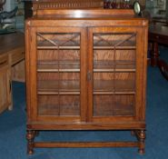 A 1930's Double Glazed Door Oak Display Cabinet On Turned Legs with a cross stretcher. 41'' in