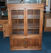 A Golden Oak Double Door Glazed Display Cabinet with the mock jacobean style with 2 linen fold