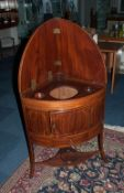 A Mahogany Inlaid Sheraton Period Corner Wash Stand with a bow front and a fitted top with three
