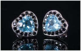 Sky Blue Topaz and Black Spinel Heart Shaped Earrings, each stud earring comprising a heart cut