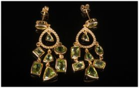 Peridot Pair of Chandelier Earrings, 10.5cts of peridot in a variety of cuts, suspended from gold