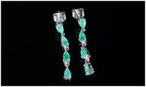 Emerald Articulated Drop Earrings, each earring comprising four pear cut emeralds, the top one