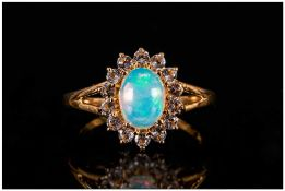 Opal and White Topaz Ring, an oval cut cabochon opal of over 1ct, with a good display of colours,