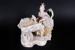 Dresden Lace Figure Of A Lady Sat At A Piano, blue stamp to base. 6.5'' in height, 7'' in length.