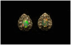 Opal and White Topaz Pair of Stud Earrings, each earring comprising a pear cut opal cabochon of .