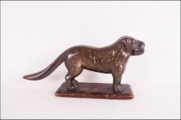 A Late 19th Century Cast Iron Novelty Nut Cracker In The Form of a Long Tailed Dog, Supported on