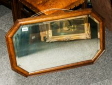 1920's Oak Framed Mahogany Mirror, with bevelled glass and measuring 29 by 18 inches.