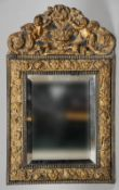 A late 18th/early 19th century Dutch pressed brass decorated wall mirror The shaped crest with