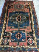A Hamadan wool rug The wine red field enclosing a stylised central medallion with pendant