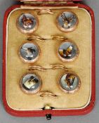 A cased set of six unmarked yellow metal mounted six crystal button studs Decorated with various