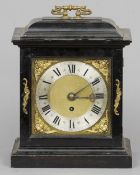 An ebonised bracket clock The 7 2/8th inch dial with silvered chapter ring, putti mask spandrels and