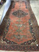 A 19th century Persian wool rug The wine red field centred with a medallion with pendant palmettes