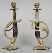 A pair of 19th century naval sword handle candlesticks Each standing on a pierced spreading base.
