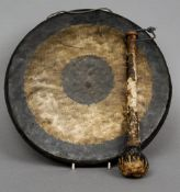 A 19th century Chinese gong and striker The verso with calligraphic script.  36.5 cm diameter.
