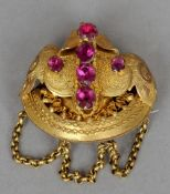 A 19th century coloured paste set Pinchbeck brooch With pendant swags.  4 cms wide. CONDITION