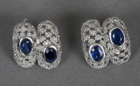 A pair of unmarked white gold, diamond and sapphire earrings Each of domed pierced form, with