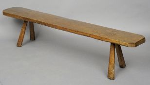 A late 18th century primitive oak bench The single plank top of canted rectangular form, standing on