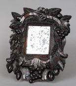 A 19th century carved walnut wall glass The rectangular plate bordered by fruiting foliate carving.