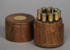 A modern black walnut place marker The case of cylindrical form, each peg formed as a cartridge.
