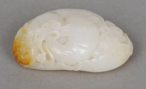 A Chinese carved mutton fat and russet jade pebble