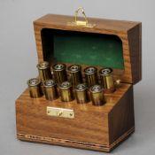 A modern black walnut place marker Of rectangular form, each peg formed as a cartridge.  9.5 cm